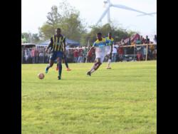 St Elizabeth Technical High School captain Antonio Biggs (right) tracks Munro College's Torain Young during their ISSA/WATA daCosta Cup game at Munro on September 14.