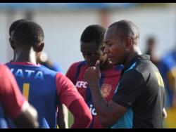 Coach of St Andrew Technical High School (STATHS) School Philip Williams (right) engages his players in a discussion during a match against Papine High School at the Edward Seaga Sports Complex on September 20, 2019.
