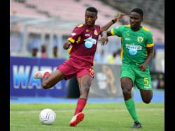 Rushan Parkinson of Dinthill (left) lines up to take a shot, while under pressure from Excelsior's Junior Parker in the ISSA Champions Cup fixture held at the National Stadium on November 1.