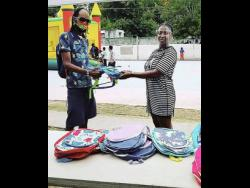 Kid Kurup hands over a school bag to a resident of Standpipe.
