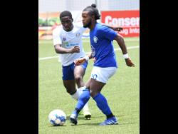 Mount Pleasant's Kemar Beckford (right) gets his pass away ahead of an onrushing Emelio Rousseau of Portmore during yesterday's Jamaica Premier League match at the  UWI/Captain Horace Burrell Centre of Excellence.  Mount Pleasant won 1-0 with Beckford getting the goal in the 40th minute.