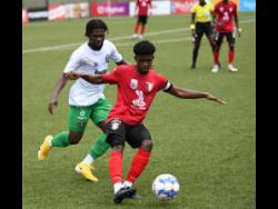 Arnett Gardens FC captain, Romeo Gutherie, controls the ball as Vere United FC goalscorer Ricardo Dennis sets himself to defend from behind during the Jamaica Premier League football match at the UWI/JFF Captain Horace Burrell Centre of Excellence yesterday. Vere won 1-0.