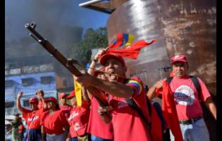 A member of the Bolivarian National Militia brandishes a rifle during an invasion drill in Caracas, Venezuela, on Saturday.