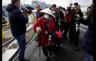 An unidentified passenger is surrounded by the media after she disembarked from the quarantined Diamond Princess cruise ship on Wednesday in Yokohama, near Tokyo. Passengers who tested negative for COVID-19 started disembarking.