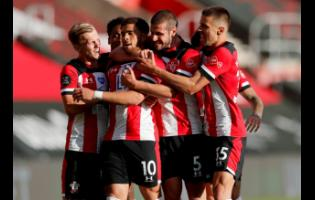 Southampton's Che Adams (second left) is congratulated by teammates after scoring his team's first goal during the English Premier League soccer match between Southampton and Manchester City at St Mary's Stadium in Southampton, England, Sunday, July 5, 2020.