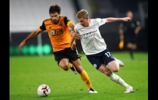 Manchester City's Kevin De Bruyne, right, and Wolverhampton Wanderers' Ruben Neves battle for the ball during the English Premier League match between Wolverhampton Wanderers and Manchester City at Molineux Stadium in Wolverhampton, England, yesterday.