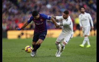 Barcelona forward Luis Suarez (left) and Real defender Sergio Ramos fight for the ball during the Spanish La Liga match between FC Barcelona and Real Madrid at the Camp Nou stadium in Barcelona, Spain, October 28, 2018.