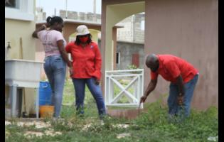 Racquel Reid-Simpson (centre), National Water Commission's wastewater supervisor, oversees an investigation of a residence during the tour.