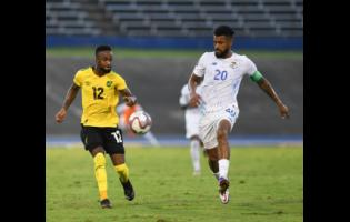 Jamaica's Junior Flemmings (left) plays the ball away while under pressure from Panama's Anibal Goday Lemus during a Concacaf World Cup qualification match at the National Stadium on September 5.