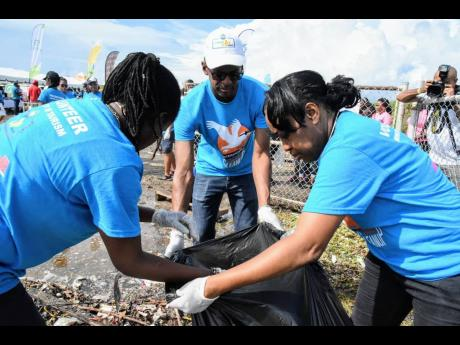 Executive Director of the Tourism Enhancement Fund (TEF), Dr Carey Wallace (centre), is assisted by TEF officers (from left) Royleta Fraser and Marva Francis to bag debris collected during a clean-up exercise on International Coastal Cleanup Day , September 21, on the  Palisadoes coastline.