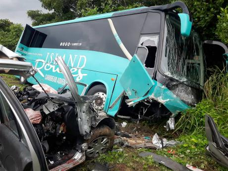 The mangled wreck of the Nissan March motor car and Island Routes King Long bus that collided along the North Coast Highway in Trelawny, where four persons died.