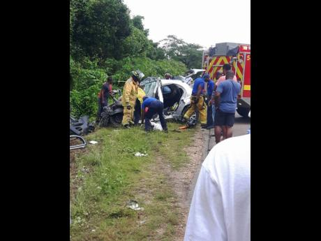 Firemen from Trelawny extricating Alecia Greenwood from The Nissan March involved in an accident, where four persons died.