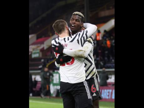 Manchester United's Paul Pogba (right) celebrates after scoring during the English Premier League soccer match between Burnley and Manchester United in Burnley, England, Tuesday, January 12, 2021.