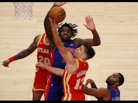Bogdan Bogdanovic of the Atlanta Hawks tries to lay-up a shot against Detroit Pistons' Isaiah Stewart in the second half of a NBA match at the State Farm Arena in Atlanta, Georgia, on December 28, 2020.