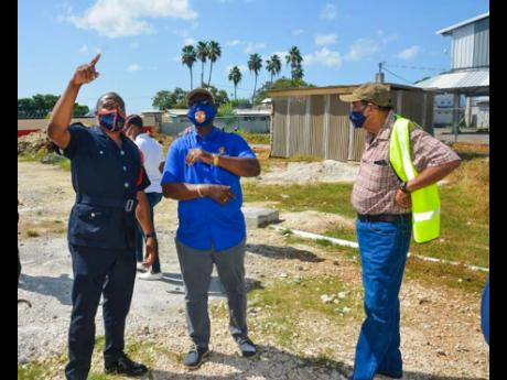 Minister of Local Government and Rural Development,  Desmond McKenzie (centre), in a conversation with Acting Senior Deputy Superintendent in charge of the Black River Fire Station, Oneil Henry (left), during a tour of the Black River Fire Station renovation project on July 16. At right is Mayor of Black River, Councillor Derrick Sangster.